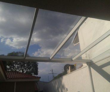 Cobertura de vidro em garagem residencial. -